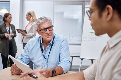 Buy stock photo Shot of a mature businessman sitting with a colleague and having a discussion while going through paperwork