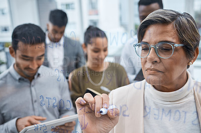 Buy stock photo Shot of a mature businesswoman writing notes on a glass screen while brainstorming with her colleagues in an office
