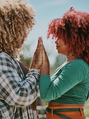 Buy stock photo Shot of two young female friends joining hands in the city