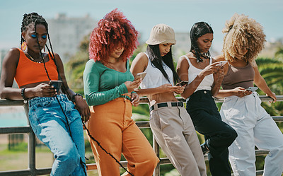 Buy stock photo Shot of a group of young friends using their phones in the city