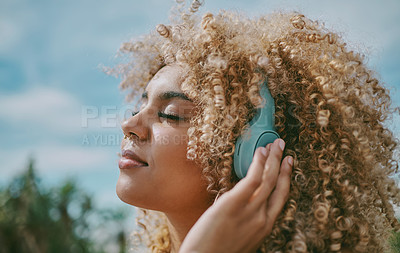 Buy stock photo Shot of a young woman listening to music in the city