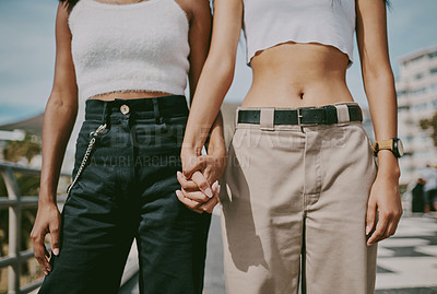 Buy stock photo Shot of two unrecognizable friends holding hands in the city