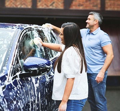Buy stock photo Shot of a couple washing their car at home