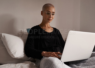 Buy stock photo Shot of a young woman using her laptop while sitting on her bed