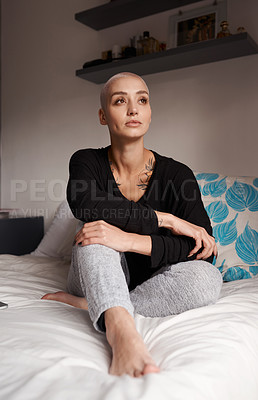 Buy stock photo Shot of a young woman looking thoughtful while sitting on her bed