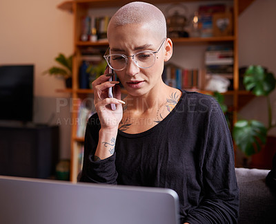 Buy stock photo Shot of a young woman looking serious while talking on her cellphone and using her laptop at home