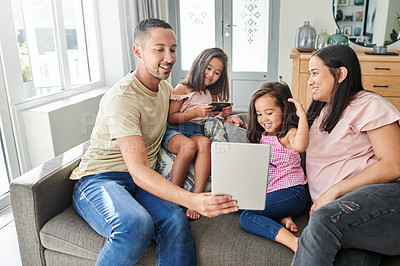 Buy stock photo Shot of a young family using a digital tablet at home