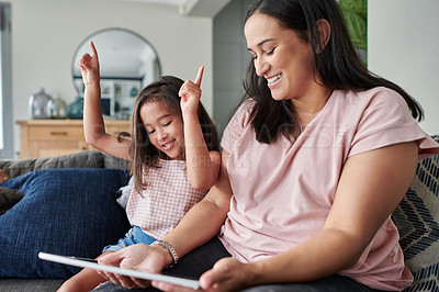 Buy stock photo Shot of a young mother and daughter using a digital tablet at home
