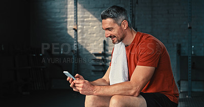 Buy stock photo Shot of a handsome mature man sitting alone in the gym and using his cellphone after his workout