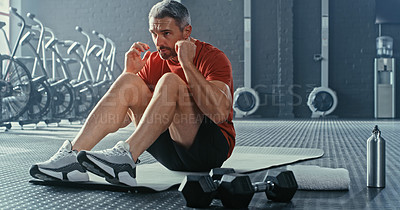Buy stock photo Shot of a handsome mature man doing sit-ups while working out in the gym alone