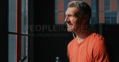 Buy stock photo Shot of a handsome mature man listening to music while working out in the gym