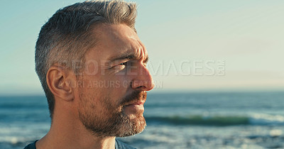 Buy stock photo Shot of a mature man looking thoughtful while exercising along the beach