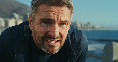Buy stock photo Shot of a mature man catching his breath while exercising along the promenade