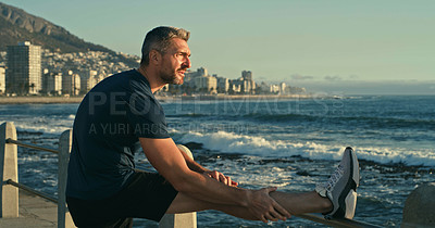 Buy stock photo Shot of a mature man stretching his legs while exercising along the promenade