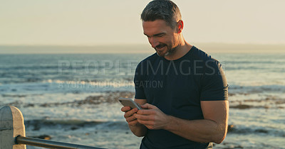 Buy stock photo Shot of a mature man using a cellphone while exercising along the promenade