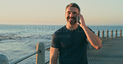 Buy stock photo Shot of a mature man talking on a cellphone while exercising along the promenade