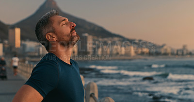 Buy stock photo Shot of a mature man taking a break while exercising along the promenade